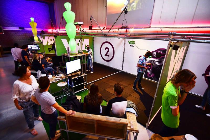 groepje mensen kijken mee op grote monitoren naar VR gamen