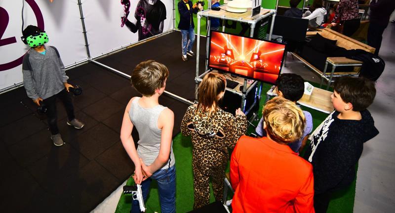 kinderen kijken mee terwijl er eentje met VR bril opstaat